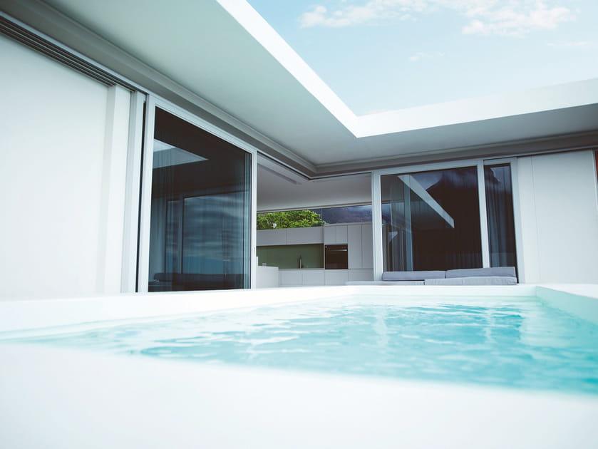 Une piscine carrée au pied de la maison