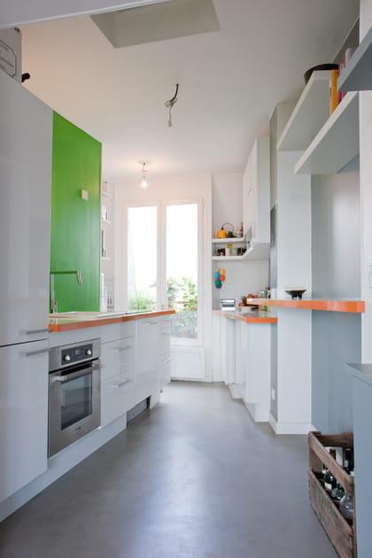 Une cuisine verte avec des touches d'orange
