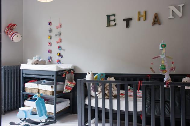 Une chambre de bébé grise avec des touches de couleurs