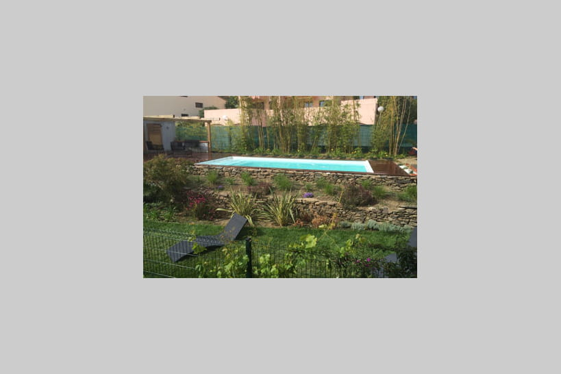 Une piscine installée dans un jardin en paliers