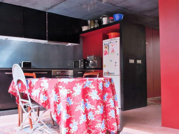 une cuisine ouverte en rouge et noir