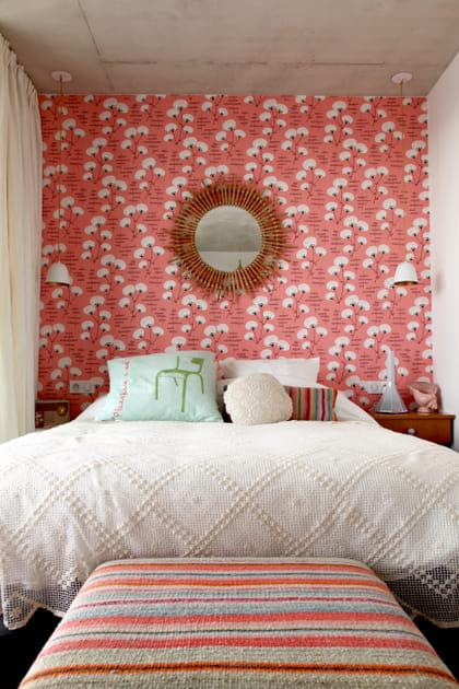 Un miroir en rotin sur du papier peint fleuri dans la chambre