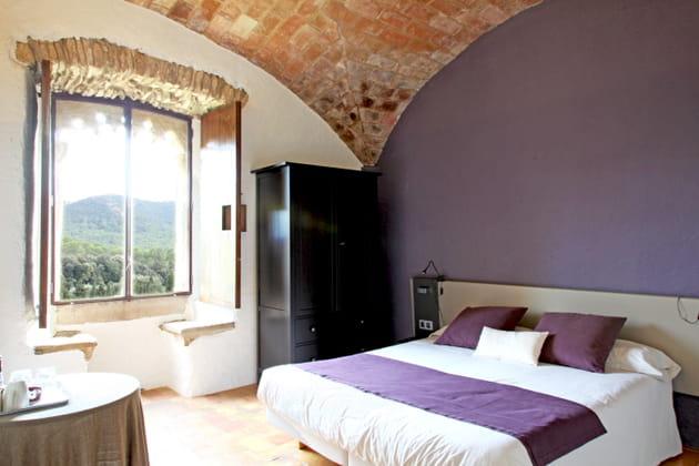 Une chambre violette sous les voûtes de pierres
