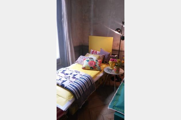 Un lit en palettes et des coussins par dizaine