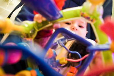 une approche tout en couleur pour ce portrait pris à travers le jouet du bébé.