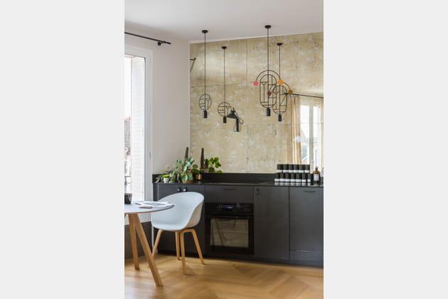Une cuisine noire rehaussée d'un miroir vieilli