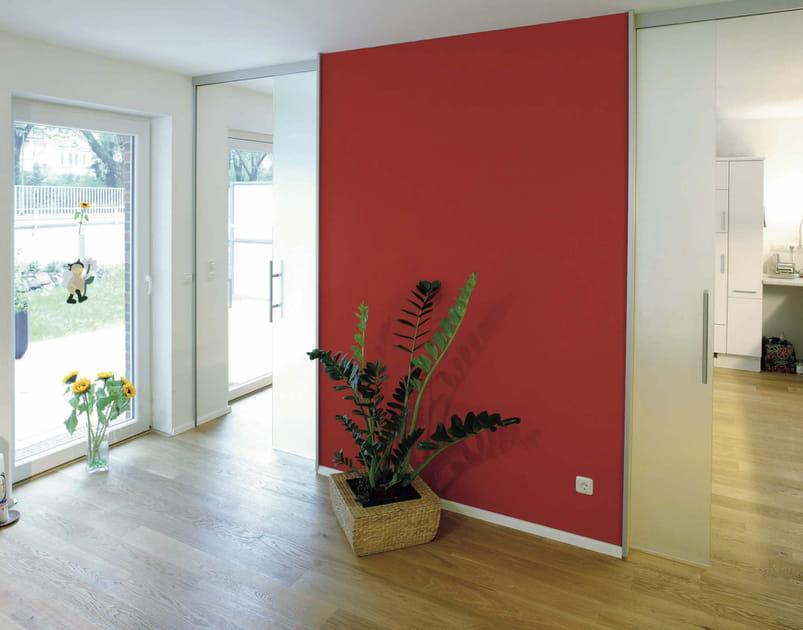 Un salon structuré par un mur rouge