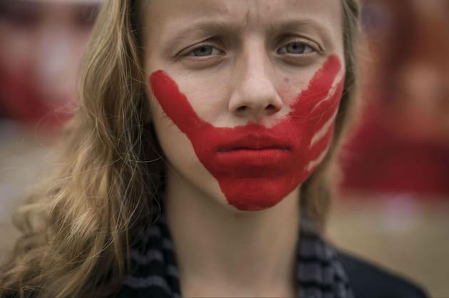 Une main rouge sur la bouche contre les violences faites aux femmes