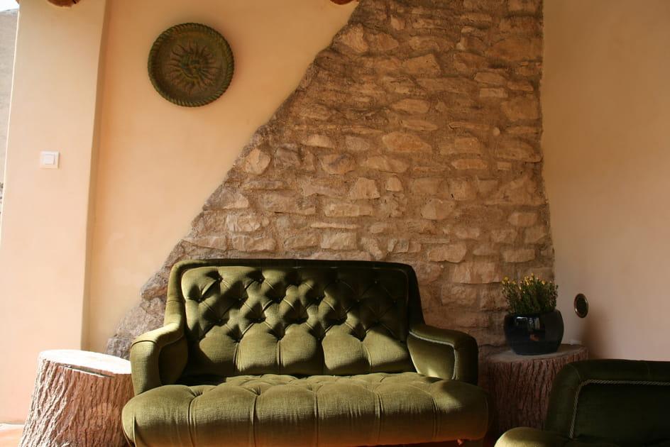 Canapé vert kaki et mur de pierres