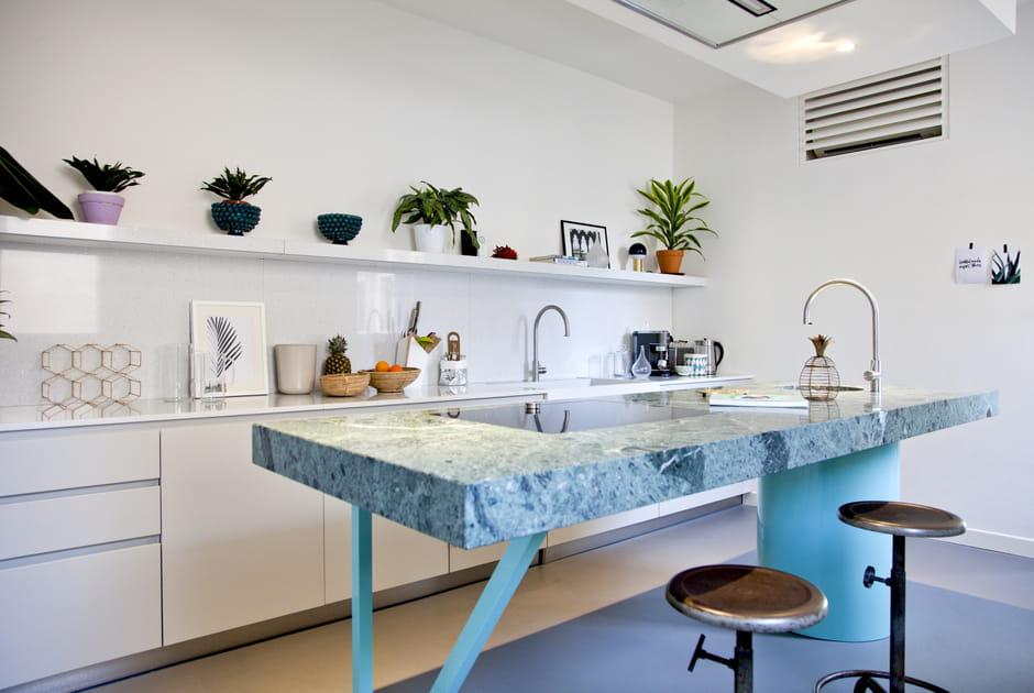 Une cuisine blanche avec îlot en pierre verte