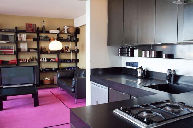 Une cuisine noire ouverte sur le salon