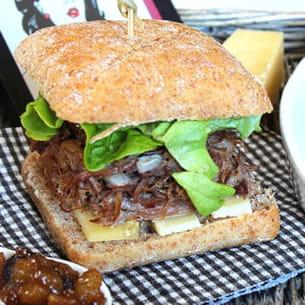burger au confit de canard, cantal, chutney de poires et brochette de pommes de