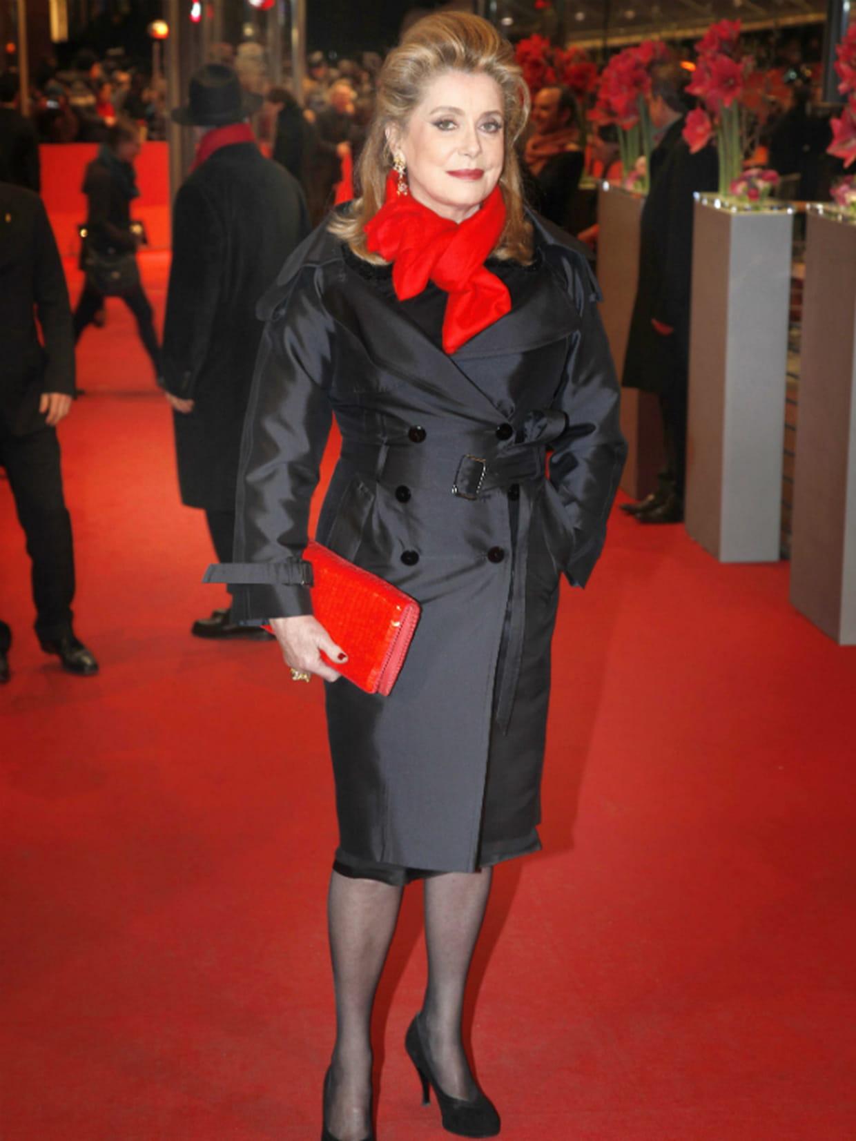 belle couleur magasiner pour l'original dernière collection Catherine Deneuve en trench et écharpe rouge