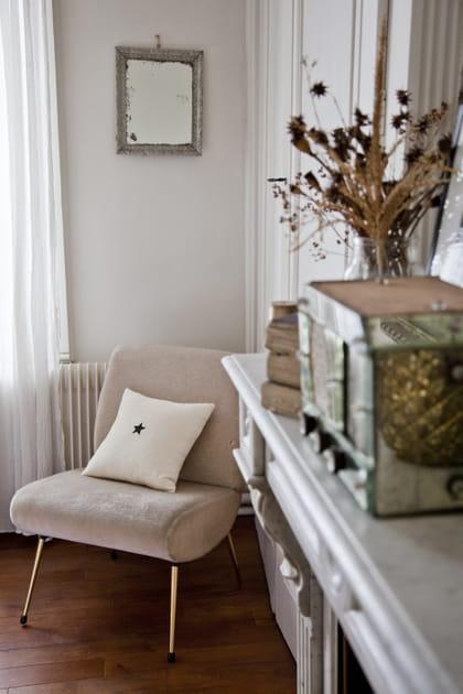 Un fauteuil en velours immaculé près de la cheminée
