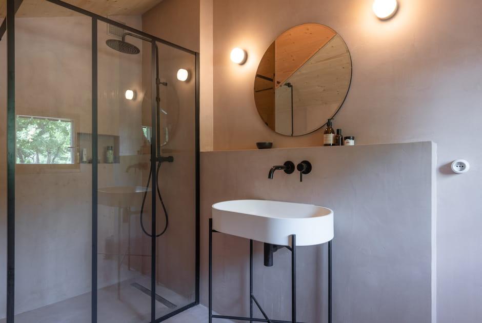 Du béton ciré au mur de cette salle d'eau avec paroi verrière