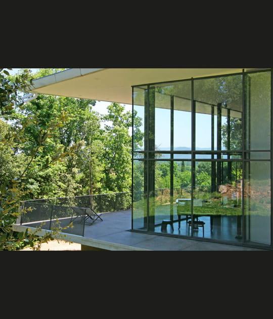 Maison de verre entre les arbres