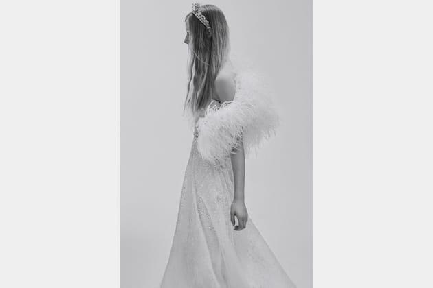 Une robe de mariée perlée avec un boléro en plumes