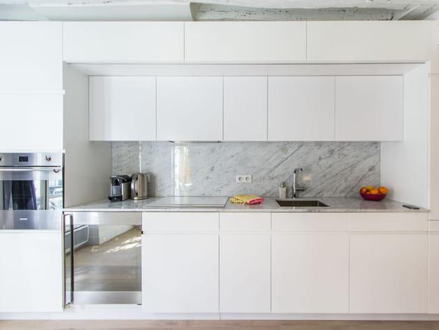 Une cuisine immaculée ouverte sur le salon