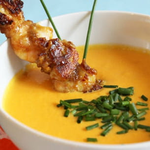 soupe froide jaune accompagnée de brochettes satay