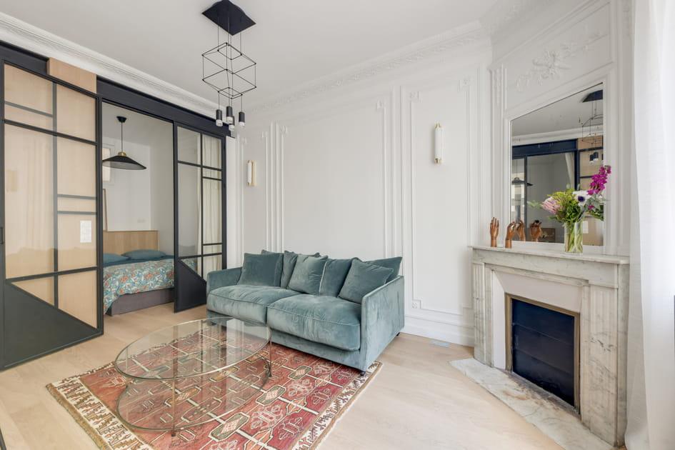 Un canapé en velours bleu gris convertible dans la pièce à vivre