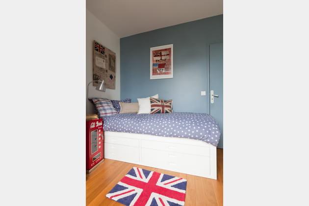 Une chambre de garçon bleue avec des touches de rouge
