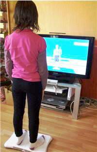 debout sur la 'balance' ou wii fit, l'enfant peutobserver ses mouvements à