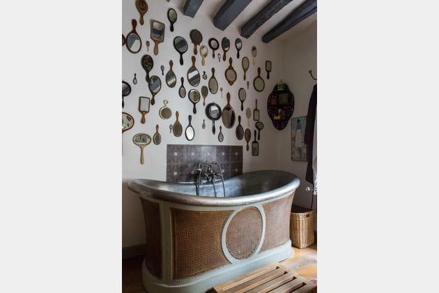 Collection de miroirs et baignoire rétro dans la salle de bains