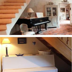 un piano à queue et un piano droit sont disposés sous un escalier