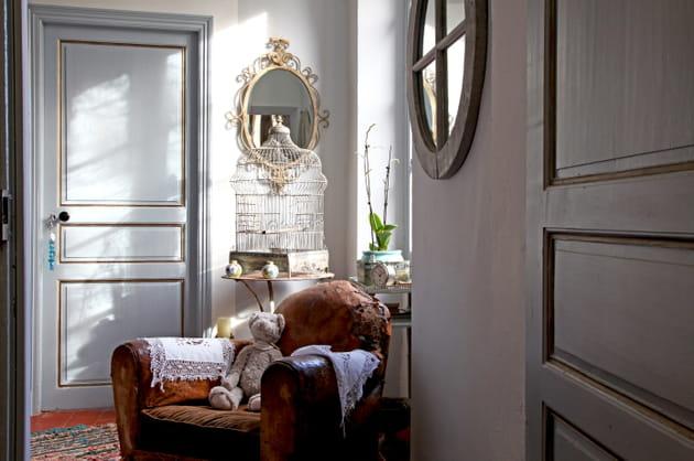 Une porte gris perle à encadrements dorés