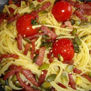 spaghettis au bacon grillé, graines de courge et tomates