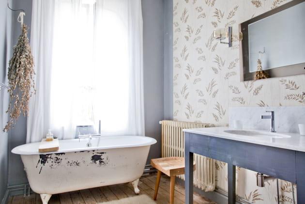 Un papier peint fleuri et des fleurs séchées dans la salle de bains