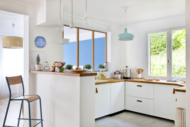 Une cuisine blanche ouverte sur la pièce de vie