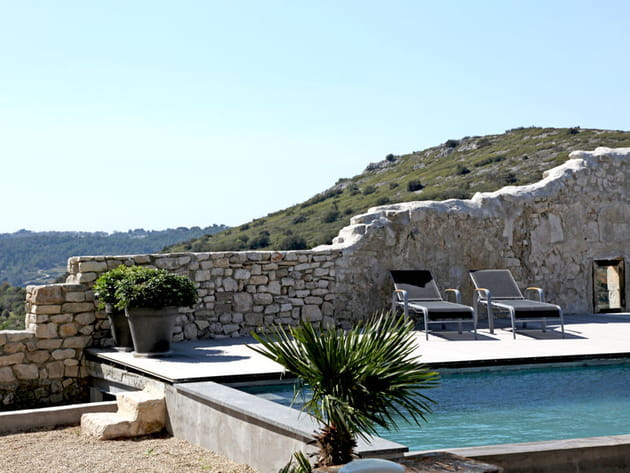 Une piscine bordée par un mur en pierre
