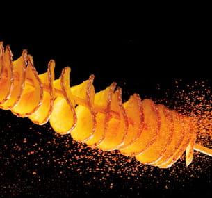 la pomme de terre est découpée en spirale avant d'être frite dans l'huile.